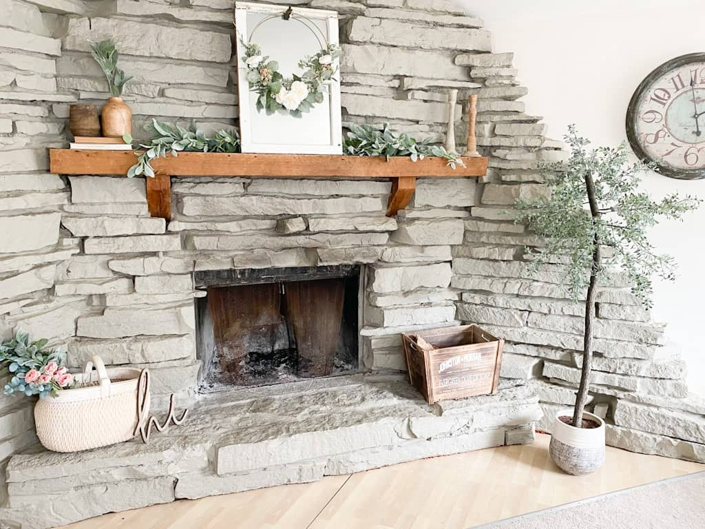 A spring home tour featuring vintage and vintage inspired pieces as well as some thrifted home decor items. This image shows a large gray stone fireplace with a wood mantel decorated with a garland, a window mirror, a spring hoop wreath, some wooden candle holders, some wooden vases on top of old books, a large white washed woven basket with a mixed floral and greenery bouquet sticking out the top, a wood crate box, and an artificial tree.