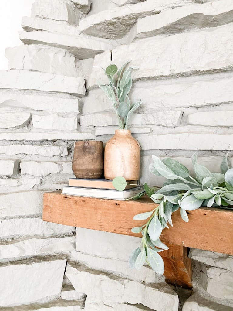 A wood fireplace mantel with two different toned wood vases on top of a stack of 2 old books.