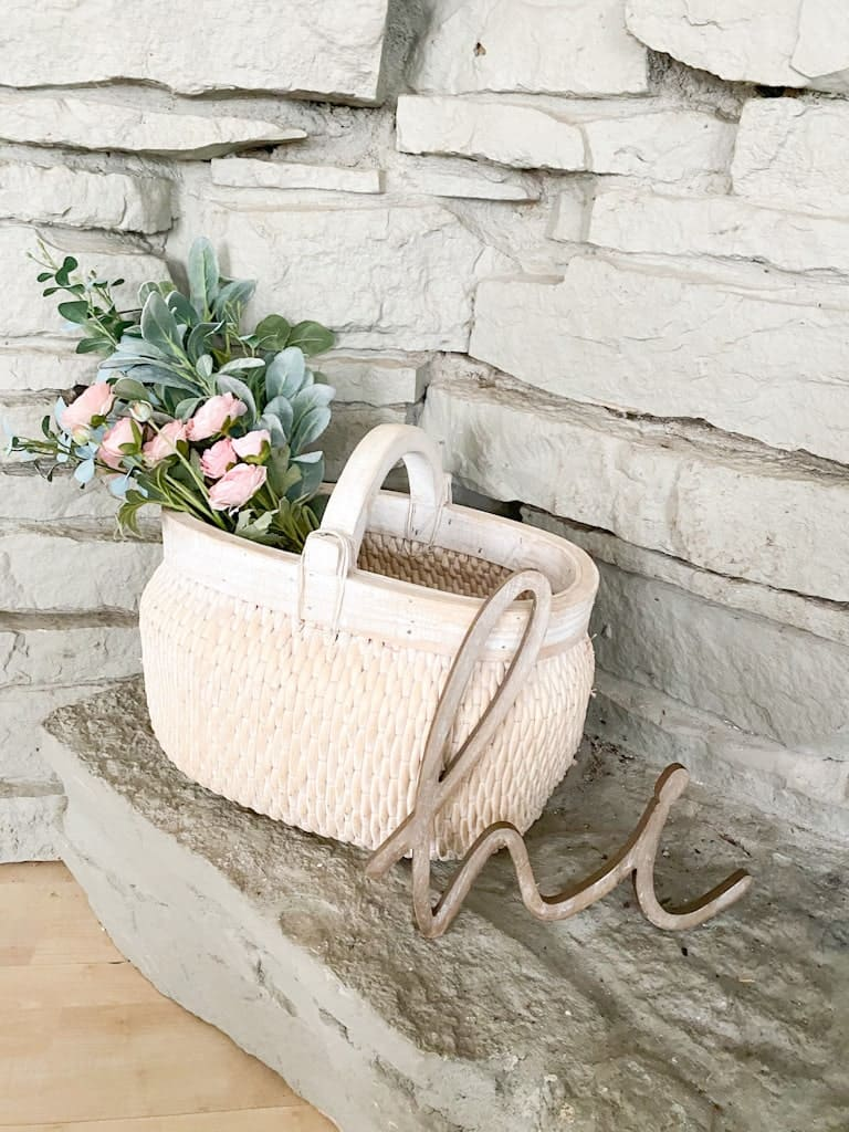 """A large whitewashed basket with a wooden handle over top that has a mixed bouquet of pink flowers and greenery inside, next to that is a wooden """"hi."""""""