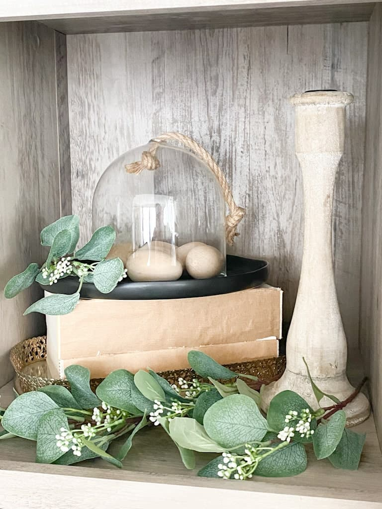 A stack of thick books with no covers on them on top of a mirrored tray with a glass cloche housing some wooden eggs on top of a black ceramic plate, next to that is a wood candlestick holder and there is seeded eucalyptus spread throughout.