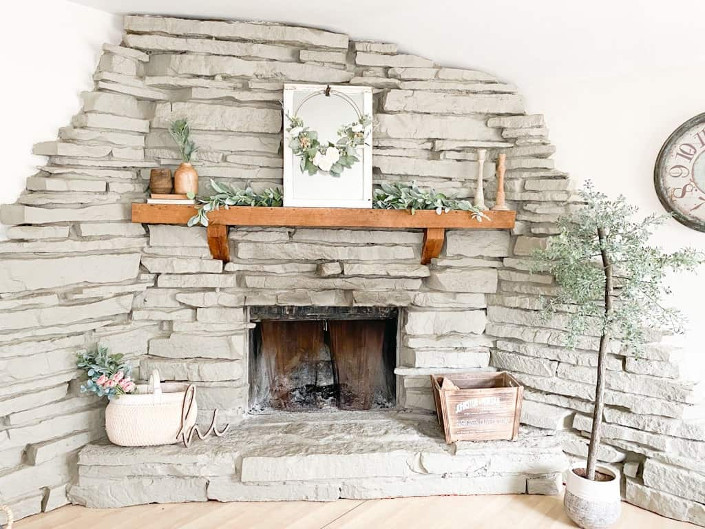This image shows a large gray stone fireplace with a wood mantel decorated with a garland, a window mirror, a spring hoop wreath, some wooden candle holders, some wooden vases on top of old books, a large white washed woven basket with a mixed floral and greenery bouquet sticking out the top, a wood crate box, and an artificial tree.