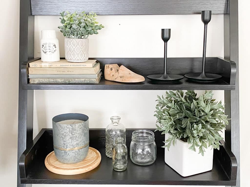 A two-tiered black wall shelf that has a stack of old books with an onld English advertising pot and a small potted plant on top, an old wooden shoe form, 2 black metal candlestick holders, a metal candle on top of a circular wood tray, 3 assorted small glass jars, and a plant in a white ceramic pot.