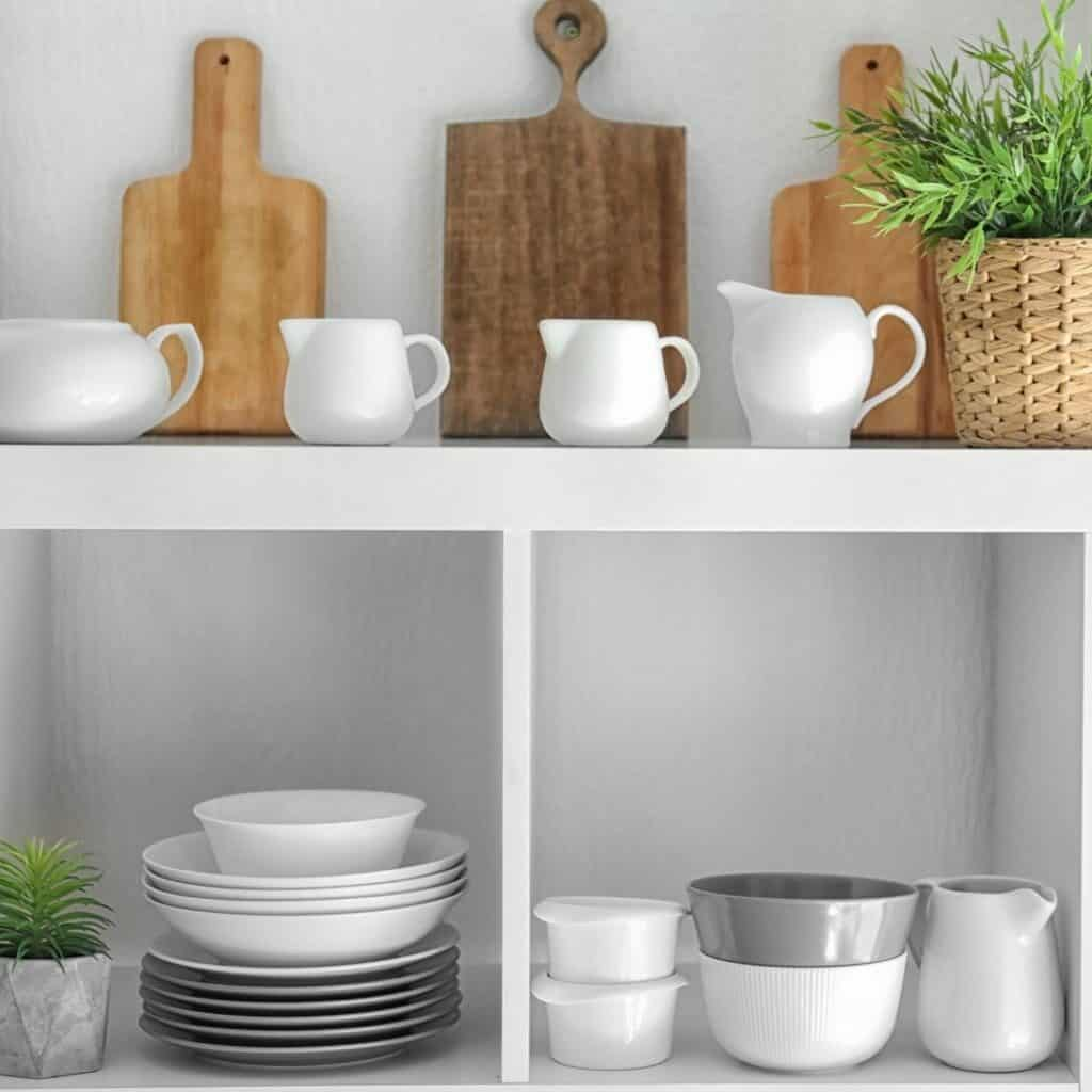 White shelves with a variety of white kitchen ware mixed with wood kitchen items and 2 plants in white pots.