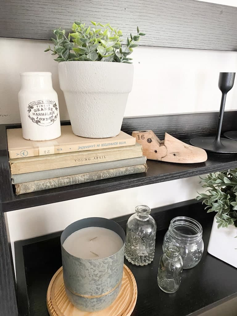 A light gray textured pot with a small plant inside next to an antique advertising jar, both are on top of a stack of old books. Next to that is an old wooden shoe form and below it are a candle in a metal holder on top of a round wood circle and some antique glass jars.