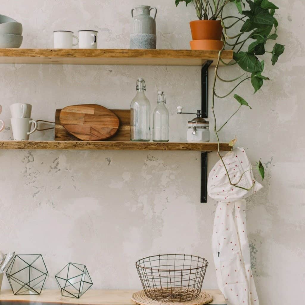 Wood floating shelves with a mixture of white and neutral colored tableware moxed with some wood cutting boards, a plant, a wire basket, and a little towel hanging off the side. A nice mixture of vintage (or vintage inspired) pieces with newer pieces are great for decorating kitchen shelves.