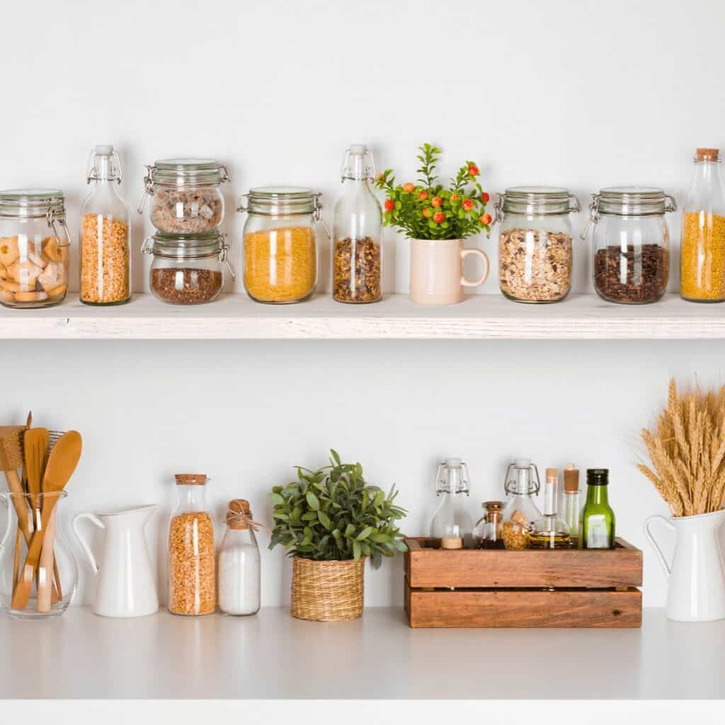 White shelves with various sized jars housing dry food items mixed with glass, ceramic, and wood kitchen items. There is a woodcrate holding some glass bottles of oils and other condiments.