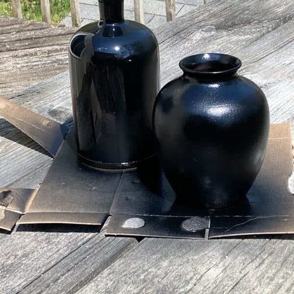 2 upcycled vases after being spray painted with 2 coats of matte black spray paint.