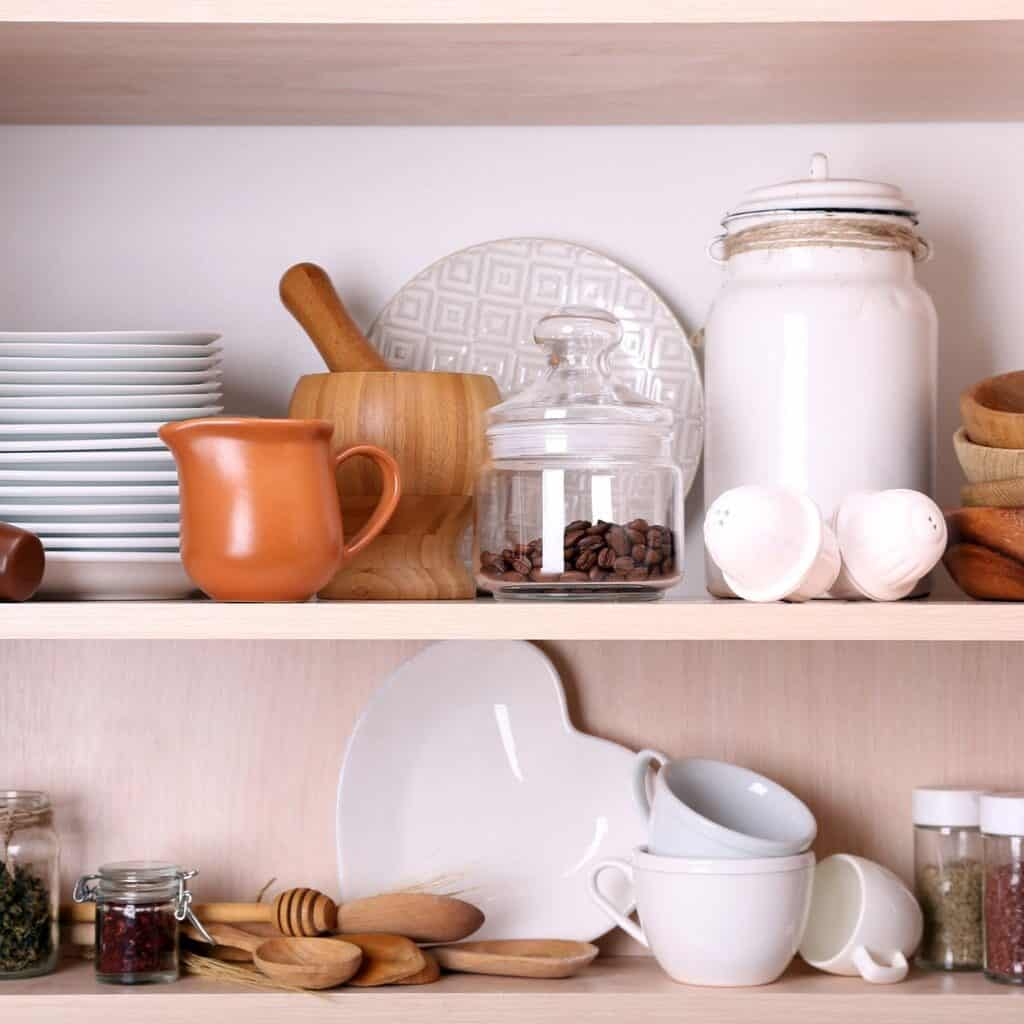 Light wood shelves with a variety of white tableware and a mixture of wood and white kitchen items. There are also some jars and jugs housing various dry food products. Perfect items for decorating kitchen shelves.