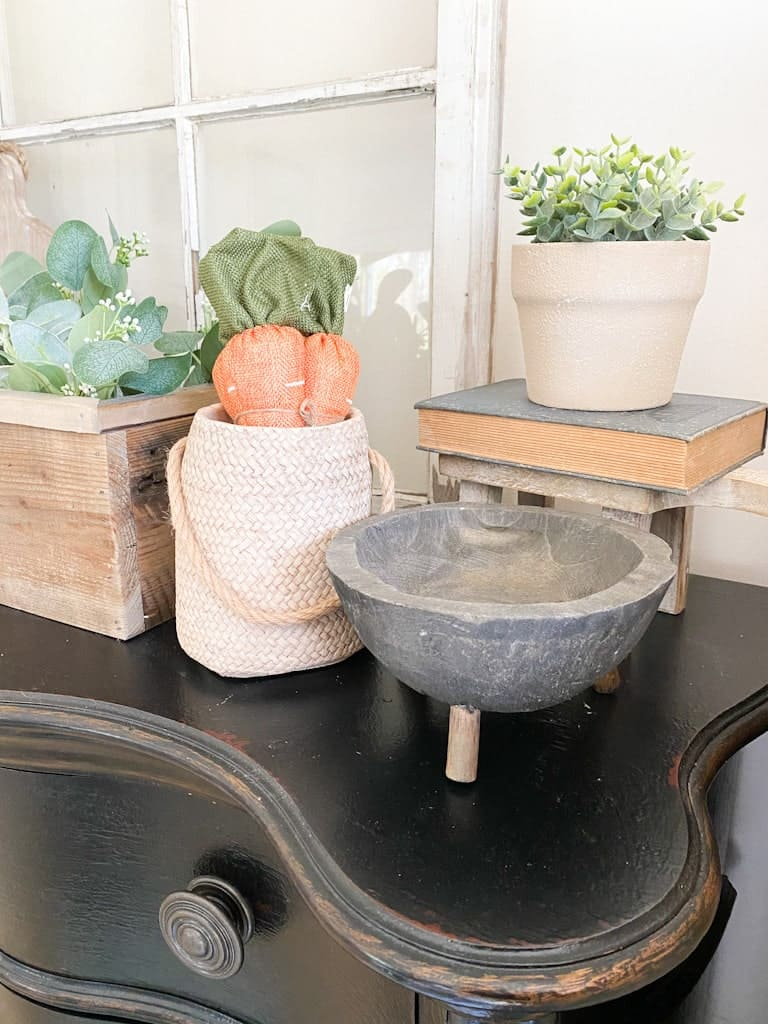 A tan textured pot with a small green plant inside on top of a book and a small stool. In front of that is a weathered black wooden bowl with legs next to a woven pottery vase with 3 fabric carrots sticking out the top of it.