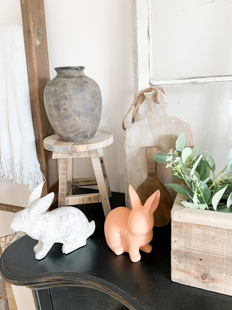 The upcycled aged pottery vase after it was finished, sitting on an old stool with a white wood bunny and a terra cotta bunny sitting in front of it.