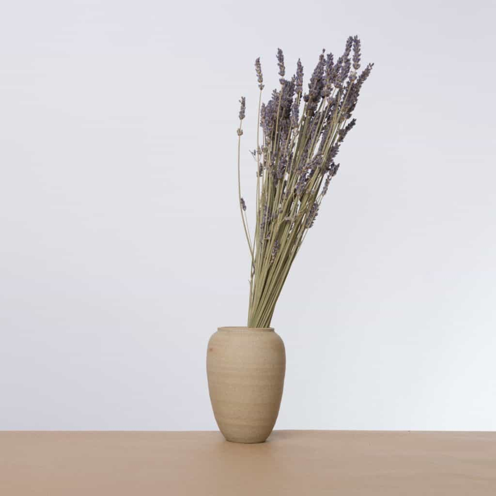 A bouquet of lavender in a beige colored ceramic vase on a wood floor in front of a white wall.