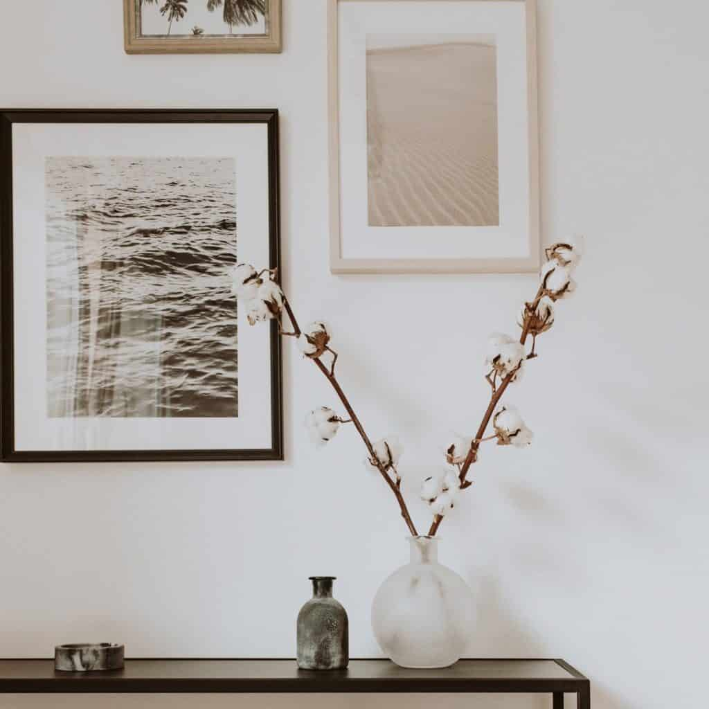A collection of 3 pieces of neutral warm toned art including some photos hanging on a white wall. In front is a small console table with a vase that has 2 tall cotton stems in it, a small glass bottle, and a littel dish.
