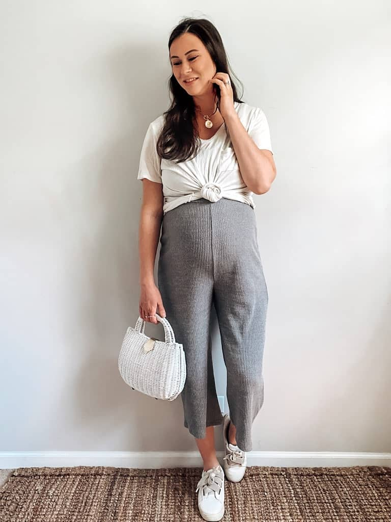 A pregnant woman wearing a gray ribbed jumpsuit with a white t-shirt over it that is knotted in front, a white wicker bag, some gold necklaces, and white sneakers.