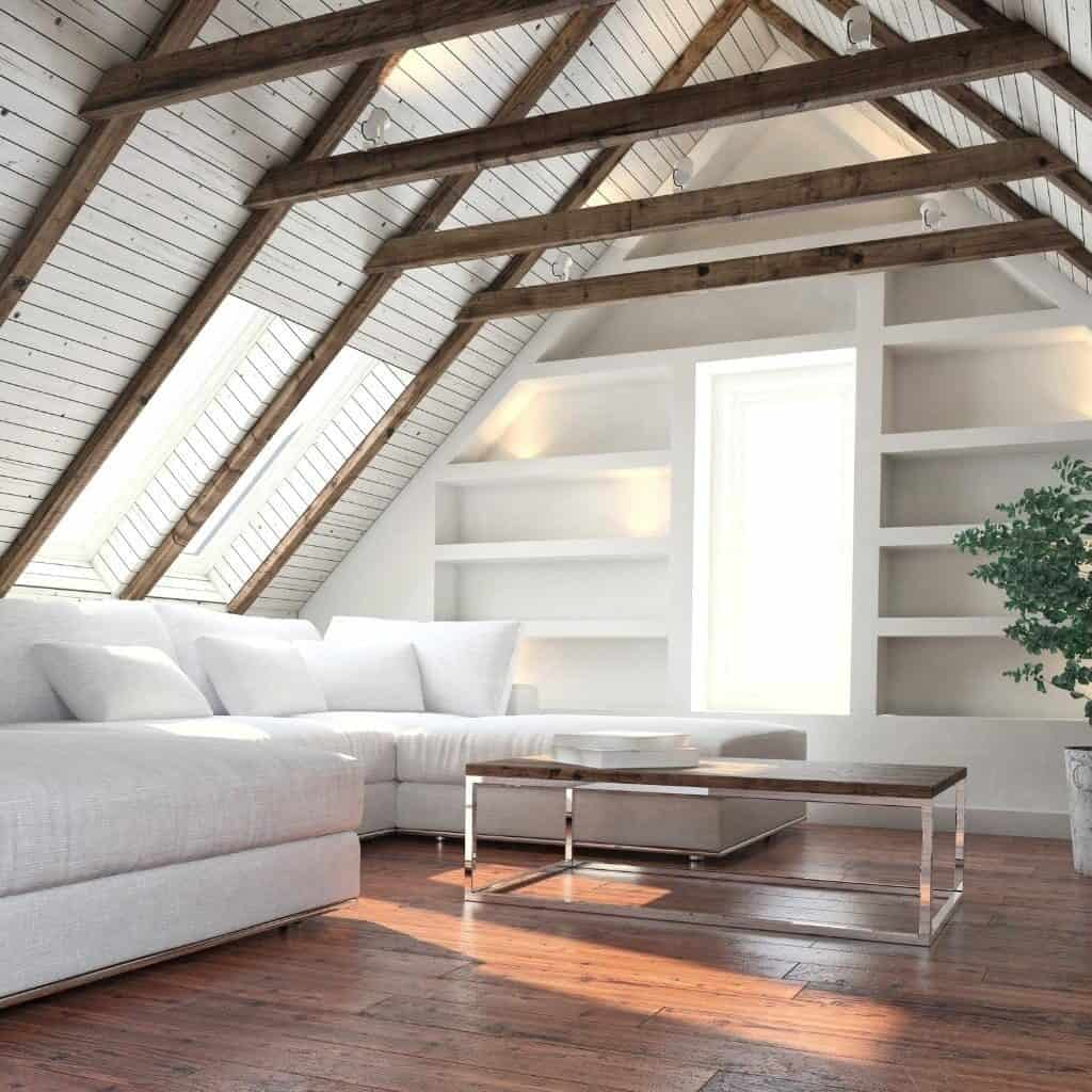 A white living room with built in bookshelfs, wood beams, wood floors, white couches, a white and wood coffee table, and a houseplant in the corner.
