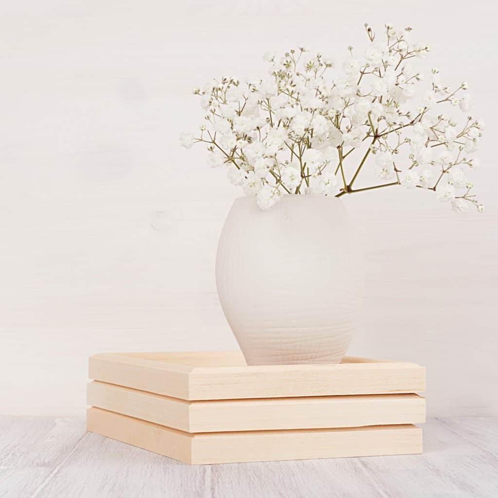 Some baby's breath in a cream vase on top of a wood box in a white room.