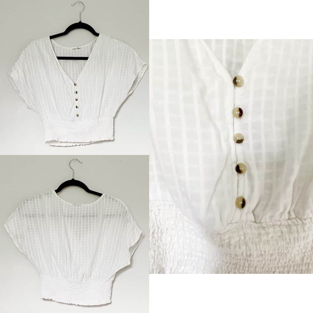 A white cropped shirt with buttons down the front and the waist is gathered.