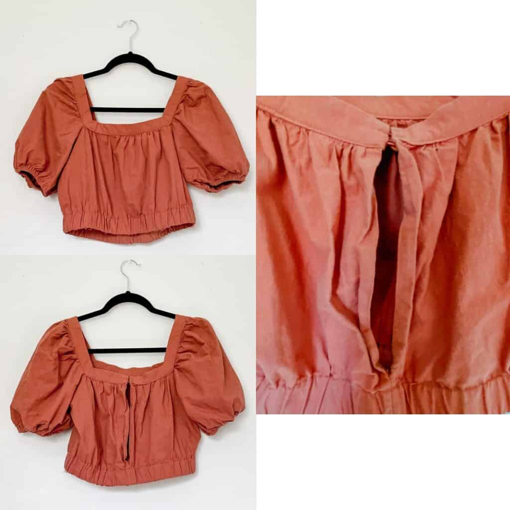 A rust colored cropped shirt with balloon sleeves that are short and an elastic waistband. There is a large keyhole in the back of the top with a 2 button closure at the top.