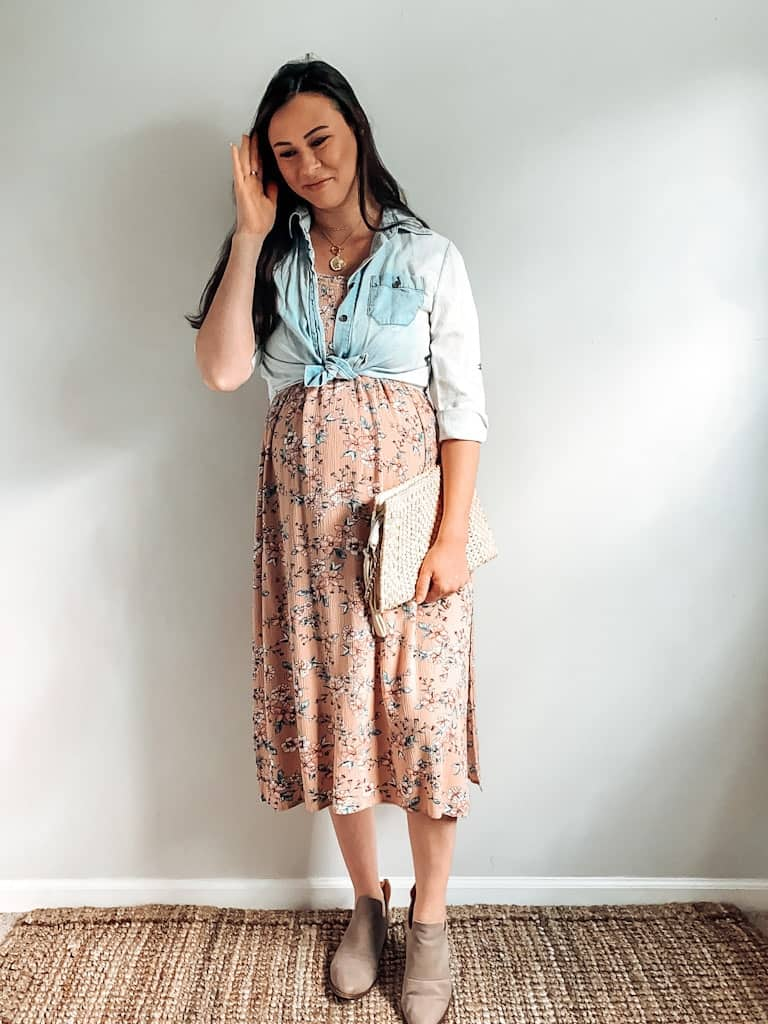 A pregnant woman wearing a pink floral midi length dress with a chambray button down shirt worn open and tied at the bottom over top of the dress, a straw handbag, some gold necklaces, and taupe ankle boots.