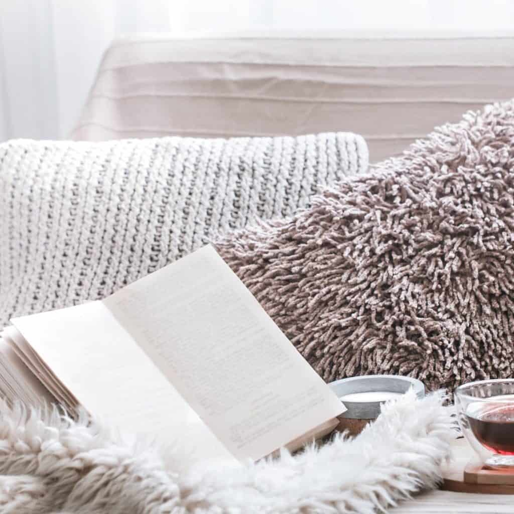 A cream knit pillow, a taupe furry pillow, and a cream furry throw blanket with an open book, a candle, and a glass of tea sit on the floor in front of a bed with a cream textured bedspread.
