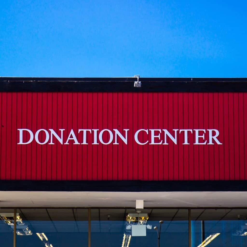 """Recycling old clothes by donating them to a thrift store. A red building with """"donation center"""" on it."""