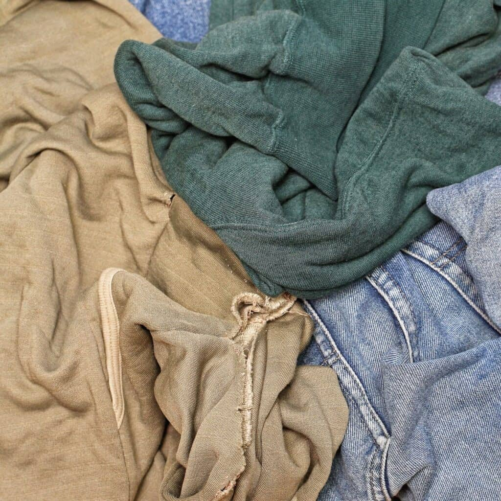 A pile of old shirts and jeans. Make them into rags to use around the house as a method for recycling old clothes.