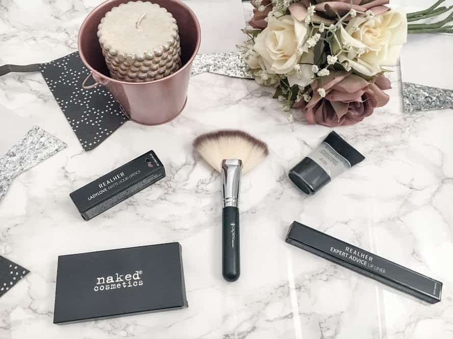 Boxycharm is a monthly beauty and skincare subscription box that would make a great gift for her. The image shows a white textured candle in a pink metal tin, some mauve and white flowers, a lipstick from the brand RealHer in its packaging, a lip liner from the brand RealHer in its packaging, a fan makeup brush from Crown Brushes, a trial size of Smashbox photo finish primer, and an eyeshadow trio from Naked Cosmetics.