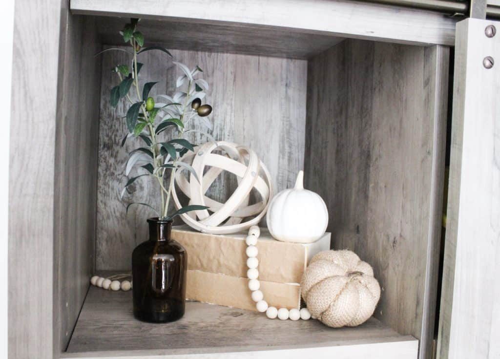 This little cubby is on our bookshelf. I added that amber vase and olive branch and the 2 different pumpkins to bring in that fall decor feel. .