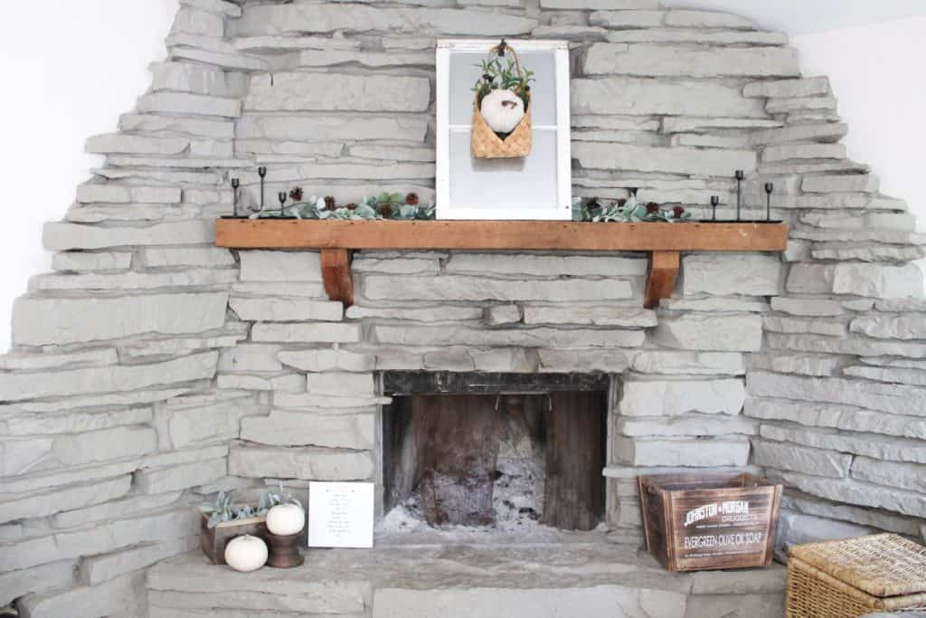 Decorating the fireplace using neutral fall decor mixed with the warmth of wood decor and pops of color from the greenery.