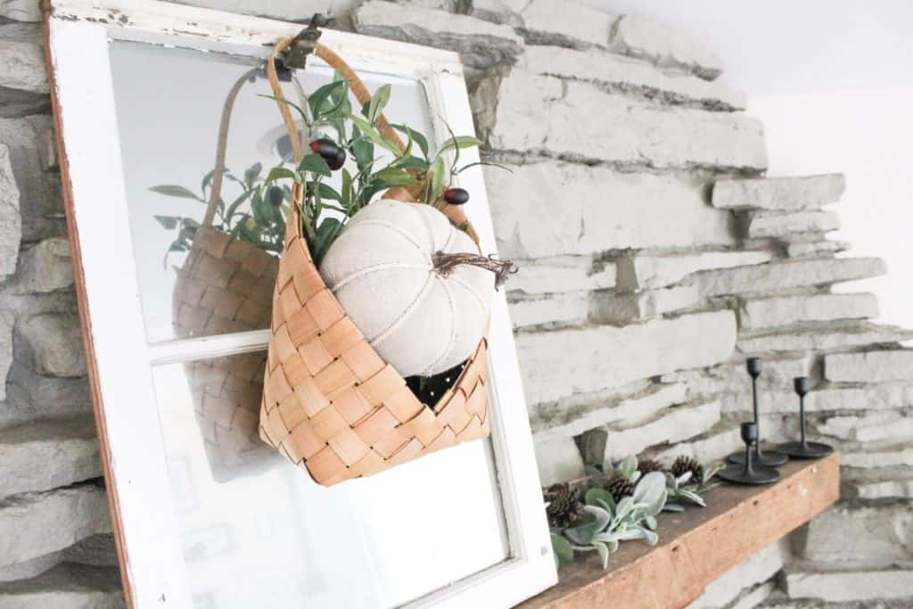 A cute little fabric pumpkin over a bed of olive branch stems sit in this adorable hanging basket. A great way to add some color to your neutral fall decor.