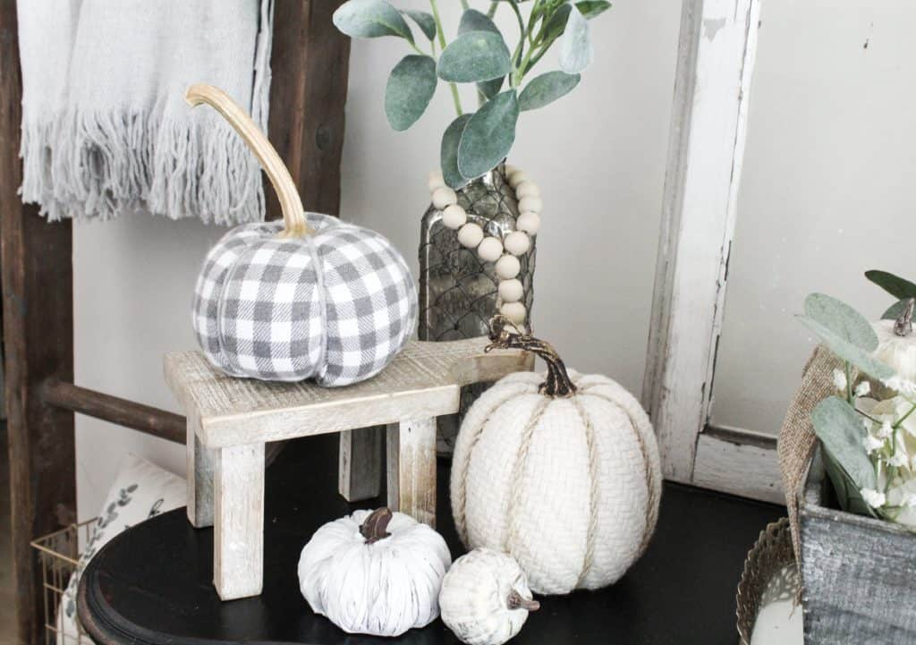 This cute collection of neutral fall decor has varying sizes, heights, and materials. I love the warmth the gingham and knit pumpkins bring while the textures of he other 2 textures add more visual interest. the touch of green with the lambs ear and the wood from the little mini stool and vintage ladder add nice touches of color.