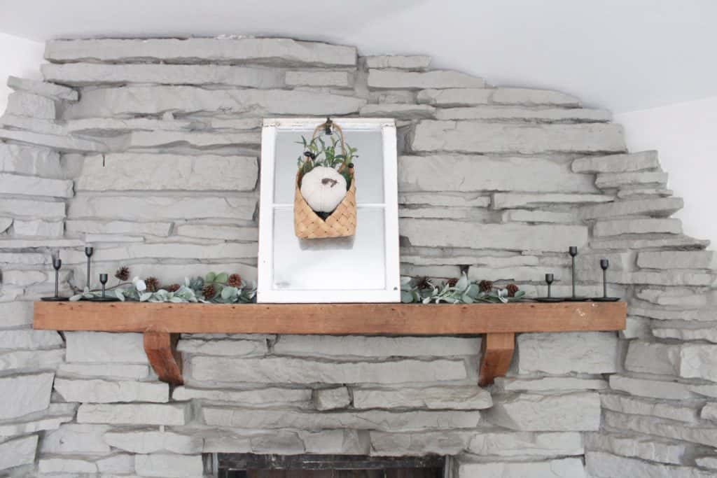 Our fall mantle decor. Netural colors mixed with the warmth of wood and he green of the faux garlands and stems.