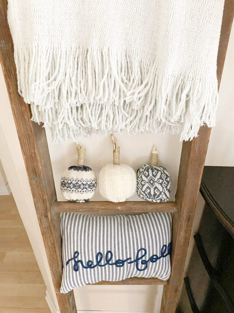 """Photo shows the 3 completed DIY sweater pumpkins sitting on an antique ladder underneath a grey throw blanket and above a blue and white striped pillow that says """"hello fall"""""""