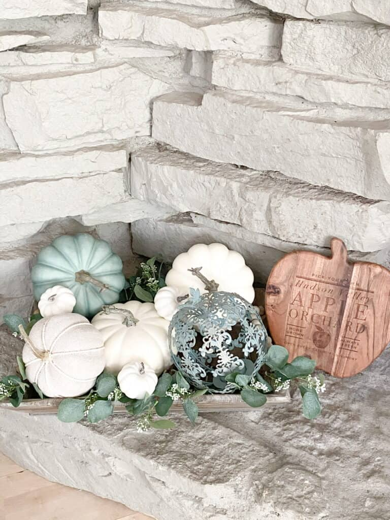 Muted fall decor, a collection of white and heirloom pumpkins mixed with eucalyptus leaves in a wooden tray. A wooden apple orchard sign.