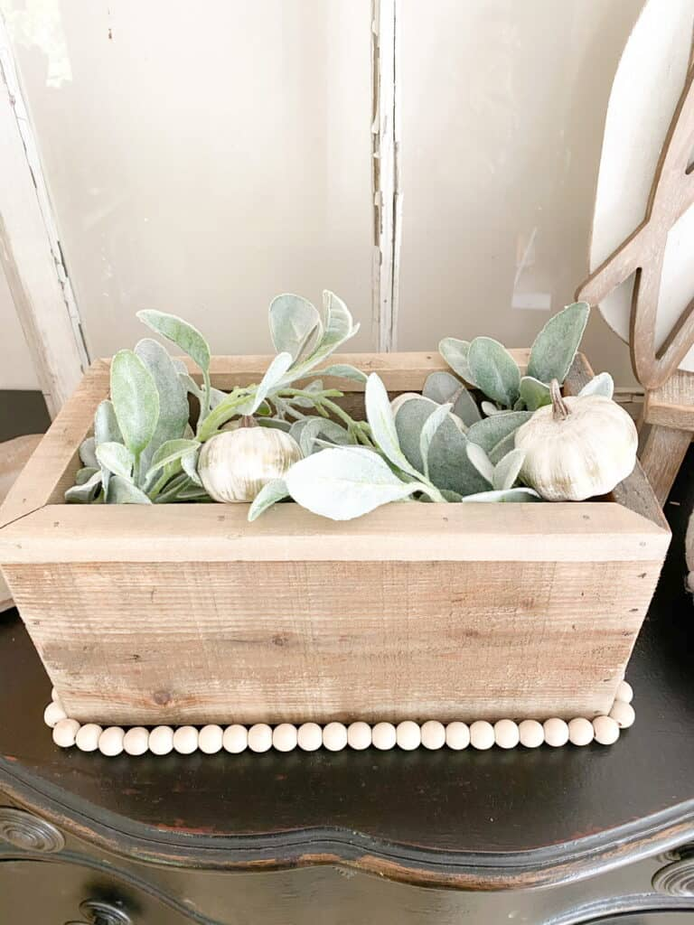 Neutral fall decor, a wooden box with a wood bead garland trim, filled with faux lamb's ear and mini white pumpkins.