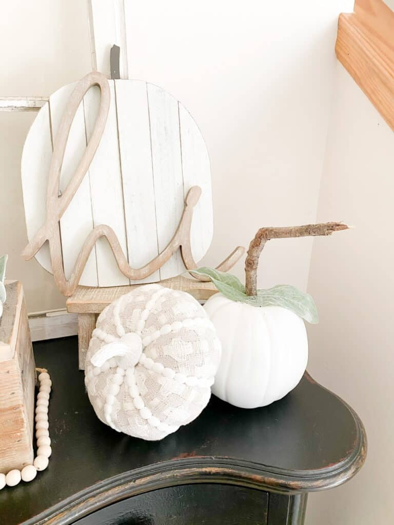 """Neutral fall decor, a white pumpkni with a stick stem, a gray and white patterned fabric pumpkin, a white wood pumpkin sign with a wood """"hi"""" in front of it."""
