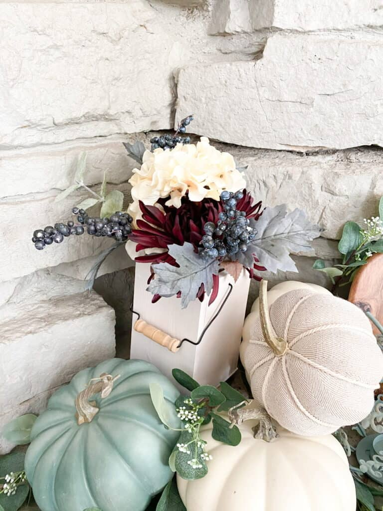 Muted fall decor, a collection of white and heirloom pumpkins mixed with eucalyptus leaves in a wooden tray. A fall bouquet of flowers in a white wooden lantern.