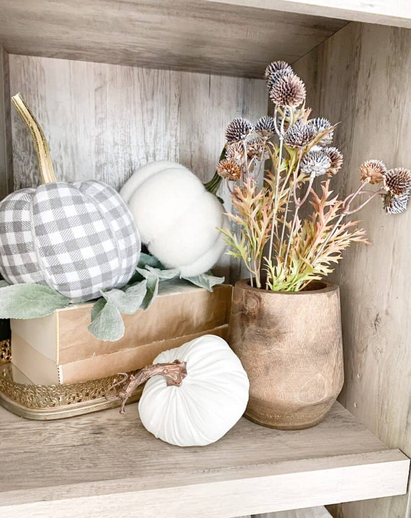 Bookshelf fall decor, a collection of different neutral pumpkins on some stacked books in a tray and a wooden vase with some fall stems inside.