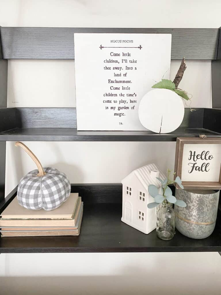Black wall shelf with neutral and muted fall decor pieces including a gingham pumpkin, a wooden pumpkin, a fall sign, and a hocus pocus sign.