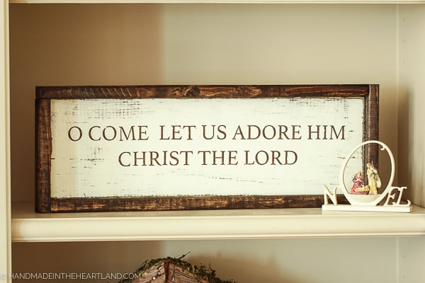 """A wood framed sign with """"O Come Let Us Adore Him, Christ The Lord"""" written on it sitting on a shelf."""