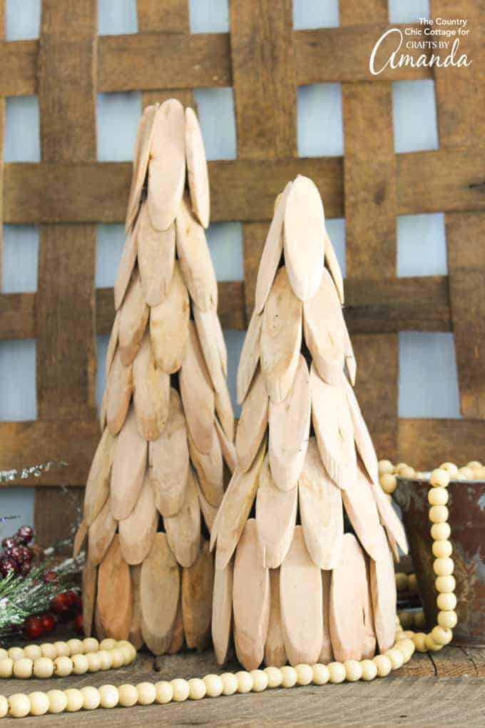 2 small Christmas trees made from slices of light colored wood set in front of a tobacco basket with a wood bead garland and some faux greenery for decoration. Such a cool neutral holiday DIY project.
