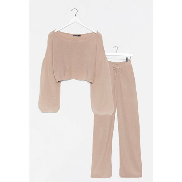 A tan knit lounge set, the top is cropped with long sleeves and the bottom is wide leg with a drawstring.