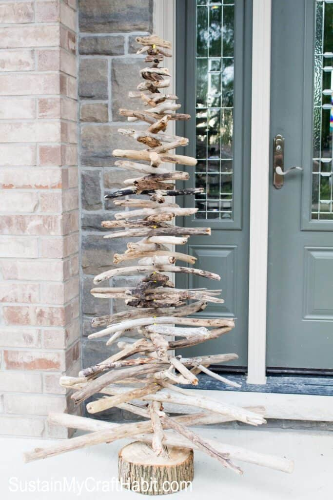 A tall outdoor Christmas tree made out of driftwood logs.