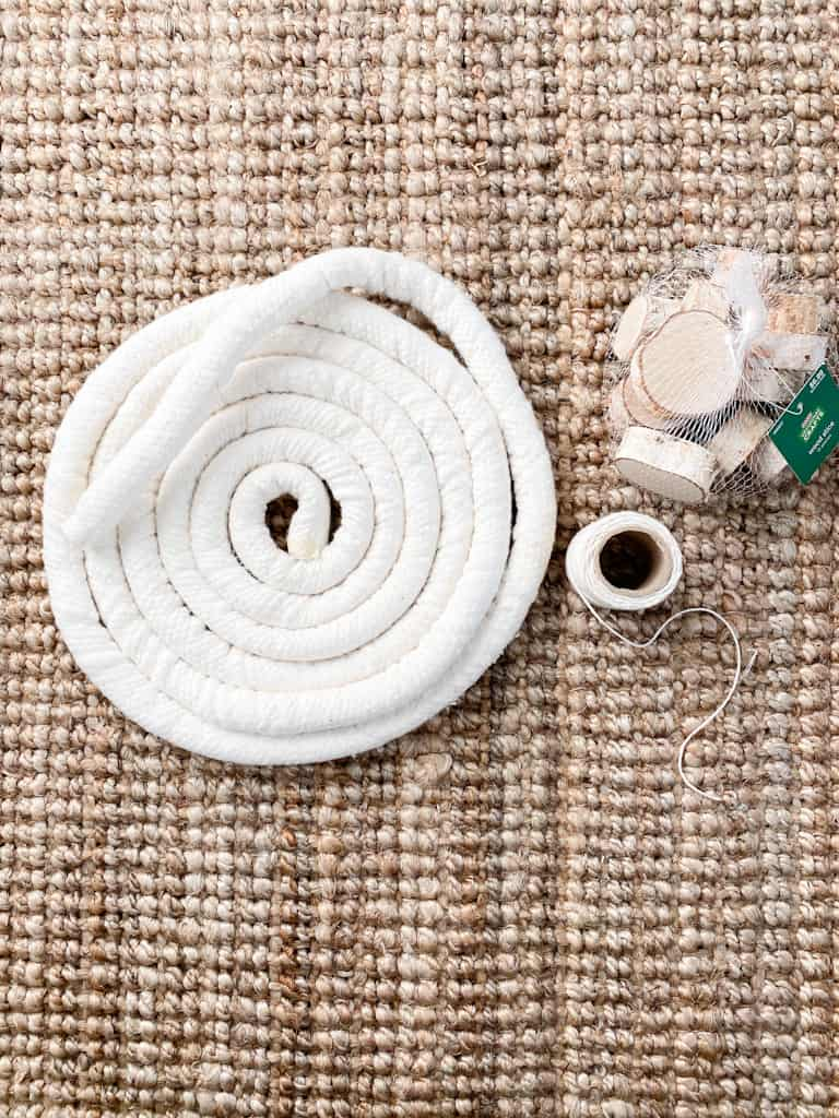 The supplies you will need for one of your DIY Christmas mantle garlands are cotton cording, birch branch slices, and cream colored string.