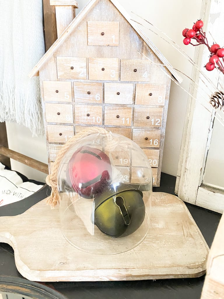 These vintage bells in red and green under a glass cloche sitting on a wood paddle cutting board add a great pop of color to these neutral Christmas decorations. Behind that display is a wooden house advent calendar.