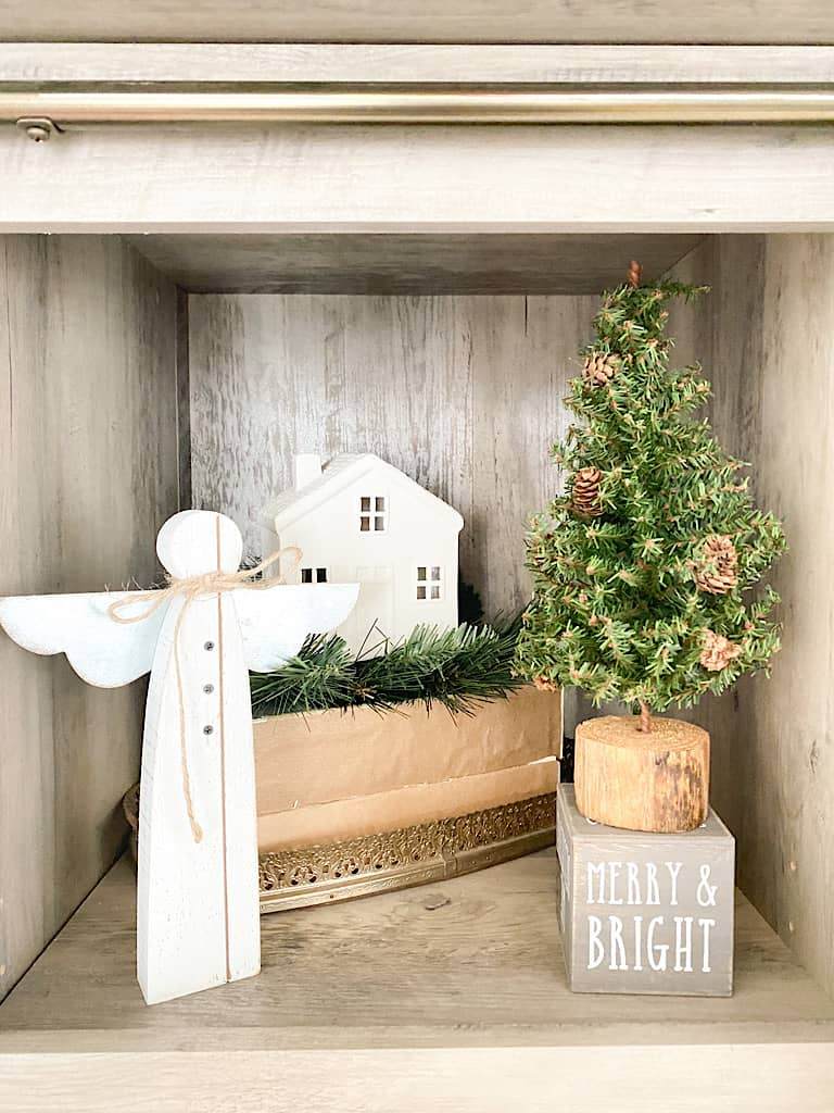 """This shelf houses a little white wooden angel, a small mini pine tree with a wooden base on top of a gray wood block with the words """"merry & bright"""" written in white on it. Behind that is a gold framed mirrored tray with a stack of 2 books on it. On top of those are some faux pine stems and a white ceramic house on top."""