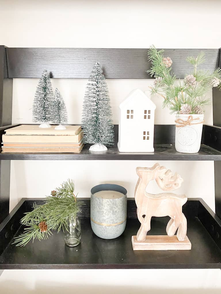 This black 2-tier shelf houses a Christmas vignette. There are some bottle brush trees on top of a stack of old books and one next to the stack of books. Next to that is a white ceramic house and then next to that is a small mason jar painted white with some twine tied around the top and there are some frosted pine branches sticking out from it. The bottom shelf has a small glass bottle that has a faux spruce stem hanging out of the top, a candle in a metal canister, and a wooden deer.