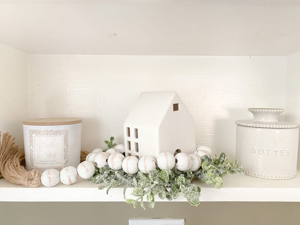 A shelf with a white jar candle with a wooden lid, a white ceramic house with a white wood bead garland wrapped around it and sitting on a small wreath of faux snowy leaves, and a small ceramic butter jar with a lid.
