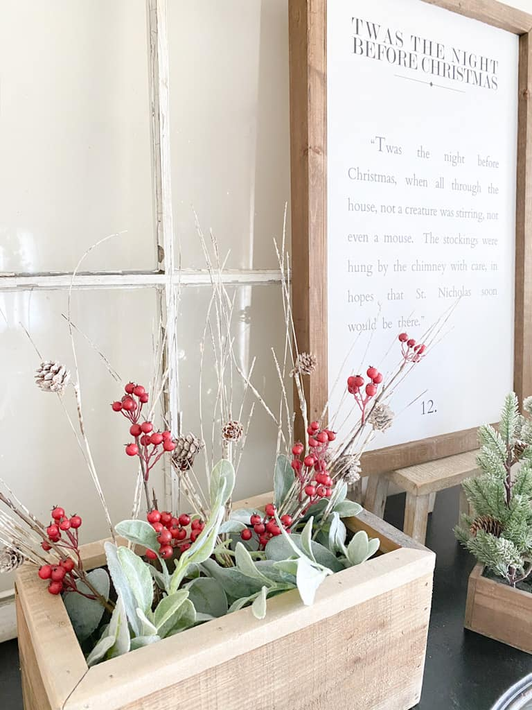 This wood box filled with faux lambs ear, faux red berry branches, and faux birch branches add lots of texture and a little pop of color to this neutral Christmas décor. Behind the box is an old window, a wood framed sign that has a passage from the Night Before Christmas sitting on a small wood stool and part of a faux pine tree is showing as well.