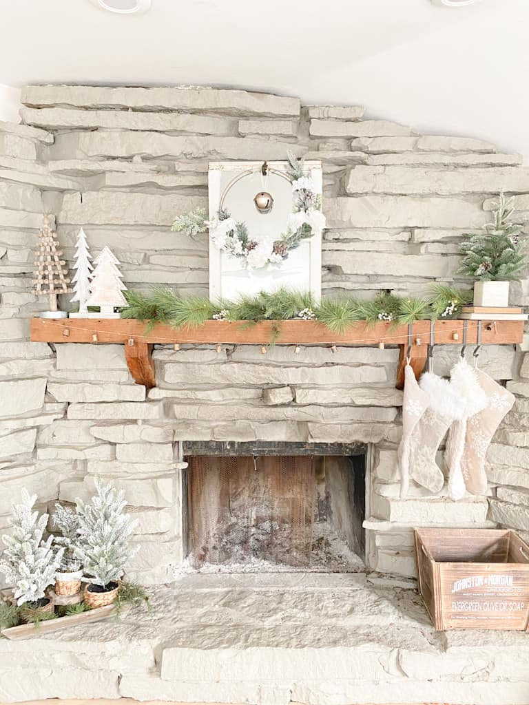 A fireplace with neutral Christmas decorations. There is an old window turned into a mirror with a hoop wreath and an old gold bell hanging from it, a set of 3 wood trees, a spruce garland, a faux pine tree in a box on top of 2 old books, 4 knit stocking hanging from black metal hooks, an antique bell garland, a wood box, and 3 mini flocked pine trees in different wicker baskets sitting on a wood tray filled with faux spruce branches.