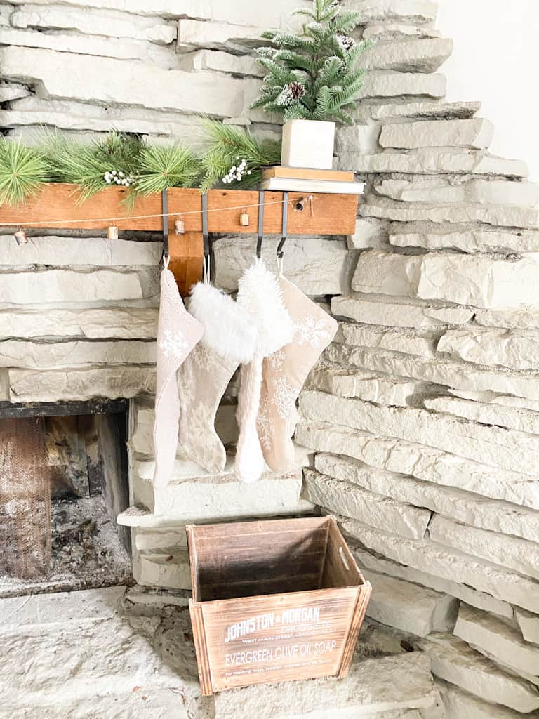 A set of 4 different knit stocking hanging from black metal hooks on a wood fireplace mantle. There is also a garland made from antique bells, a spruce garland, and a mini faux pine tree in a box on top of 2 old books. A wooden box sits below on the ledge of the stone fireplace.